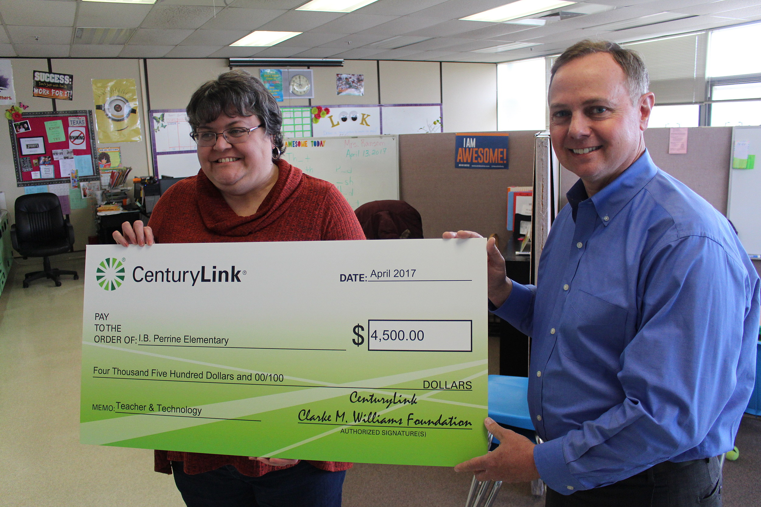 Melissa Woodland, a special needs teacher at I.B. Perrine Elementary School in Twin Falls, receives a check from CenturyLink's Jim Schmit on Thursday to help improve technology in the classroom. (Photo by Andrew Weeks)